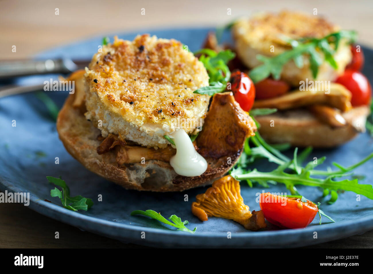 Baked goat cheese on sourdough bread with chanterelle mushrooms and cherry tomatoes - Stock Image