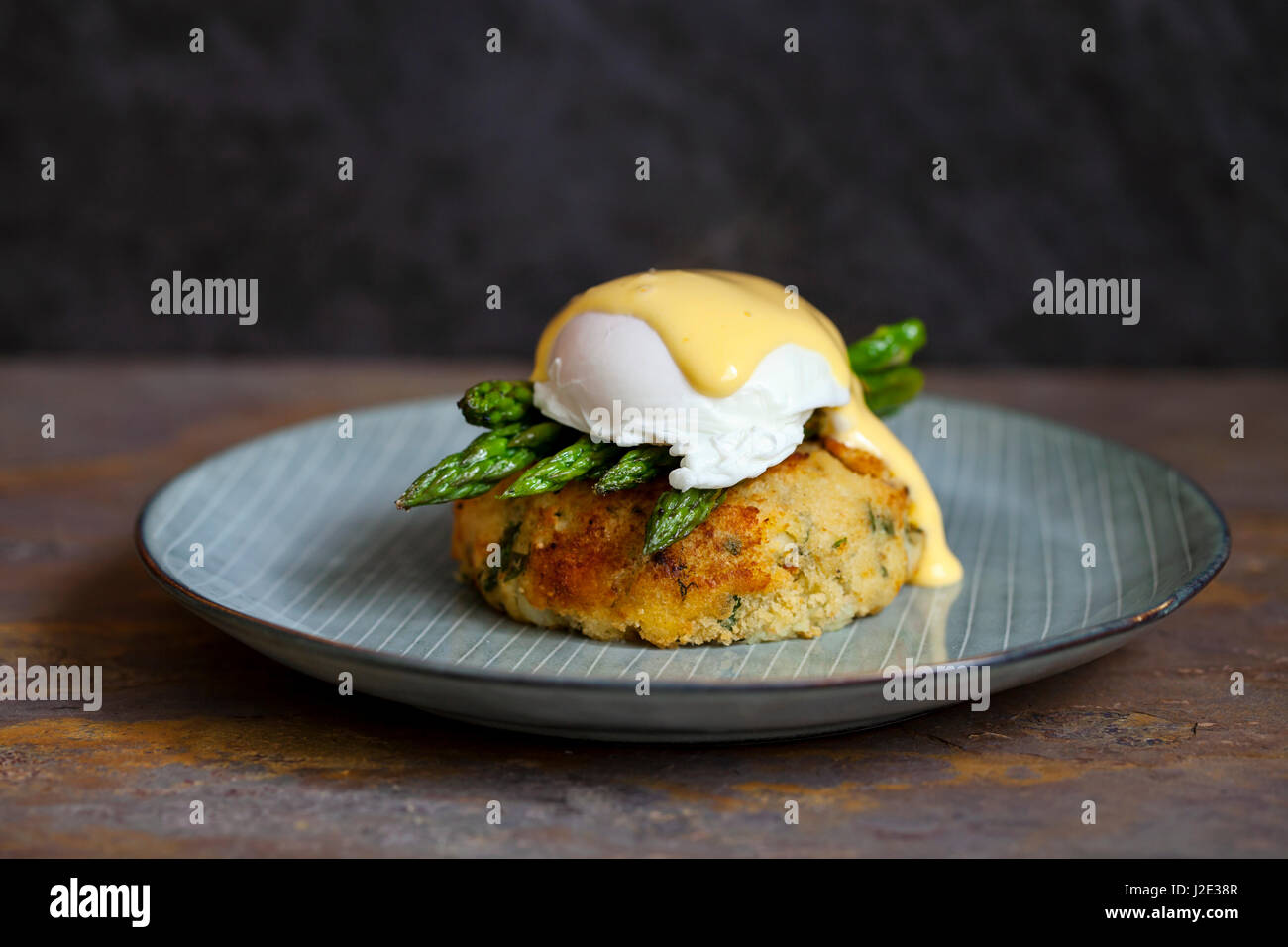 Fish cake with asparagus, poached egg and hollandaise sauce - Stock Image
