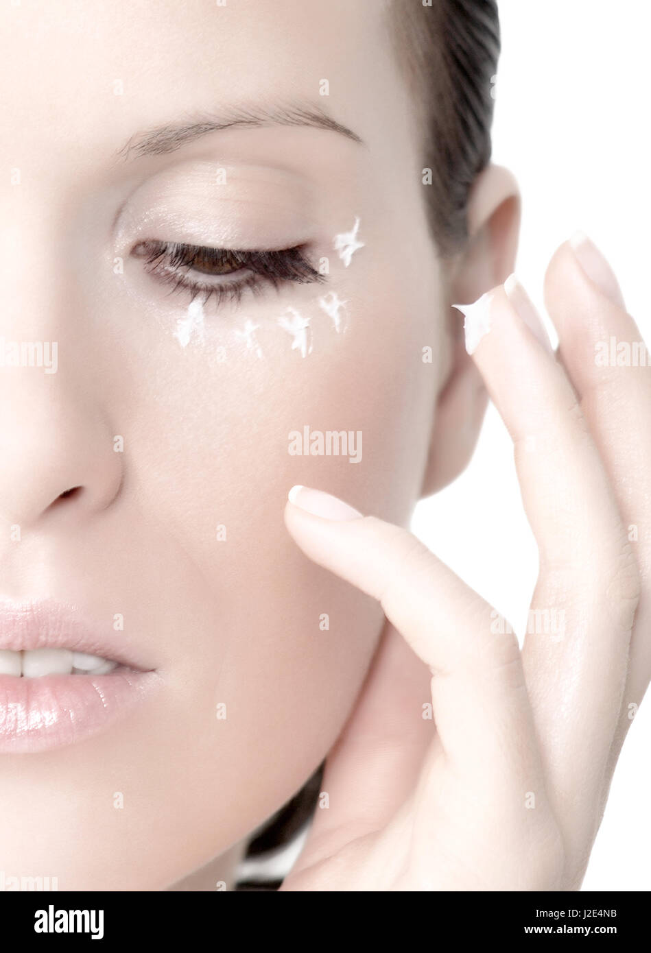 Young woman with cream under eyes and on the finger - Stock Image