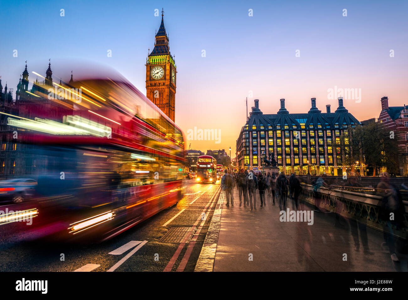 Red double decker bus in front of Big Ben, dusk, evening light, sunset, Houses of Parliament, Westminster Bridge - Stock Image