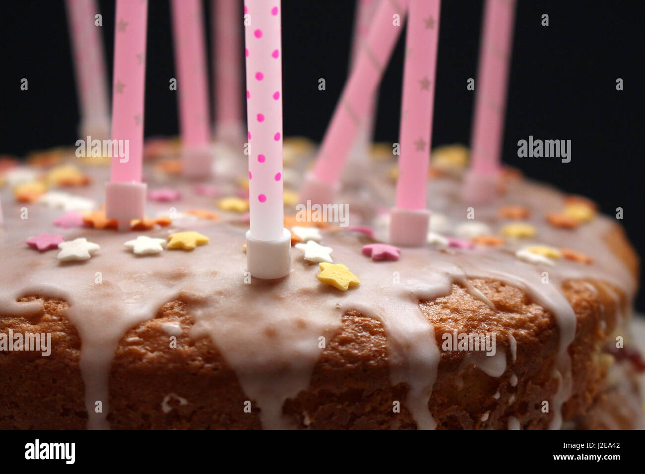 Close up view of a celebration cake, with icing, hundreds and thousands decoration, and pink candles, on a black - Stock Image