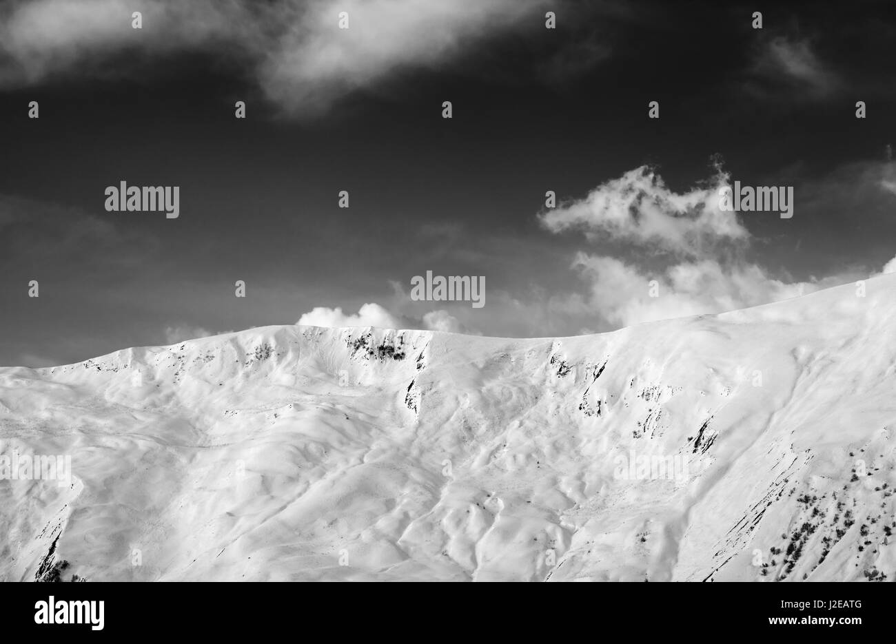 View on snowy off-piste slope. Caucasus Mountains, Georgia, region Gudauri. Black and white toned landscape. - Stock Image