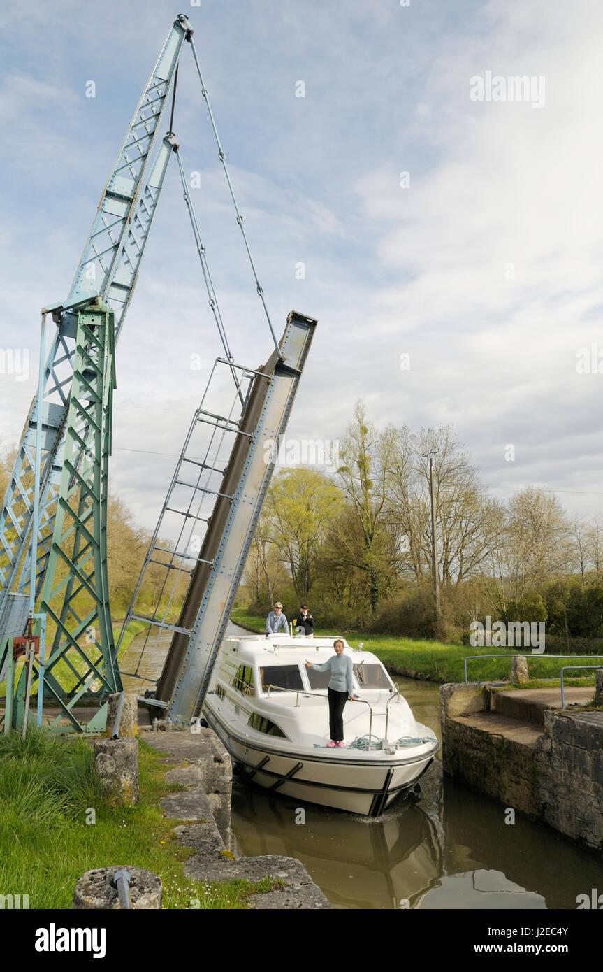 France, Burgundy, Nievre. Canal boat passing under the draw bridge, Pont levis a St Didier, Les Ilottes, Saint-Didier - Stock Image