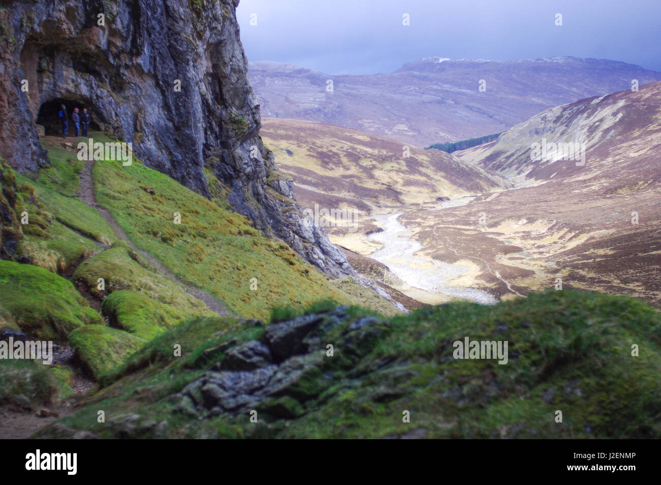 People stand in the Bone Caves, with view into the valley, Scotland. A popular low level walk.  popular with geologists - Stock Image