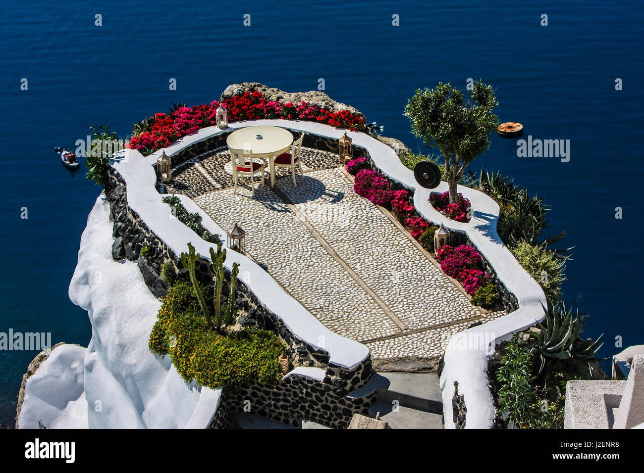 Oia, Santorini, Greece. Jutted Patio, Table And Chairs, And Floral, Cactus  Landscaping Off Of The Caldera