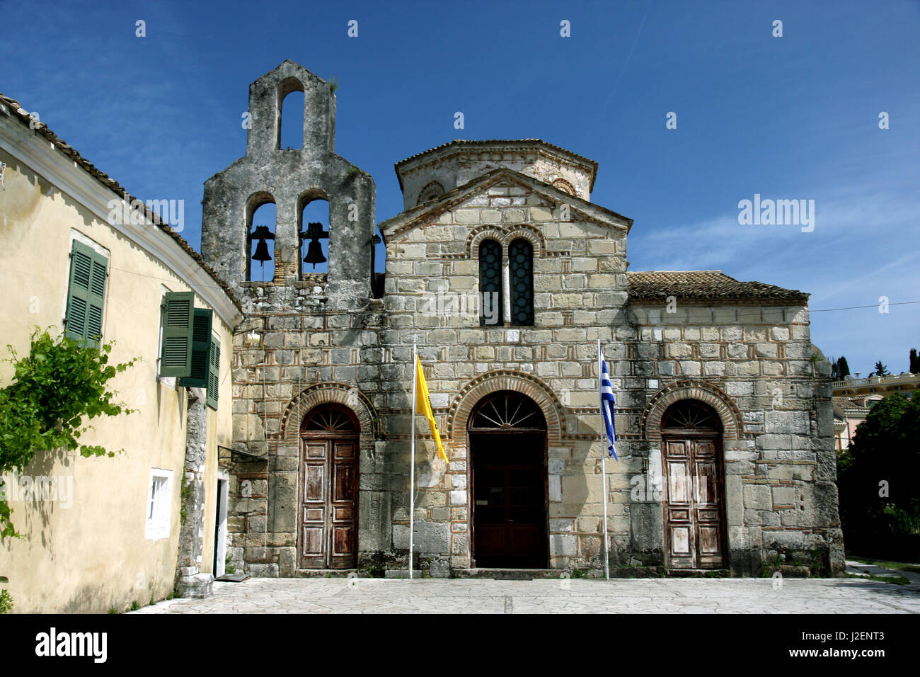 Corfu, Greece. Stone Greek church with bell tower and arched doors and windows, and Greek Flags - Stock Image