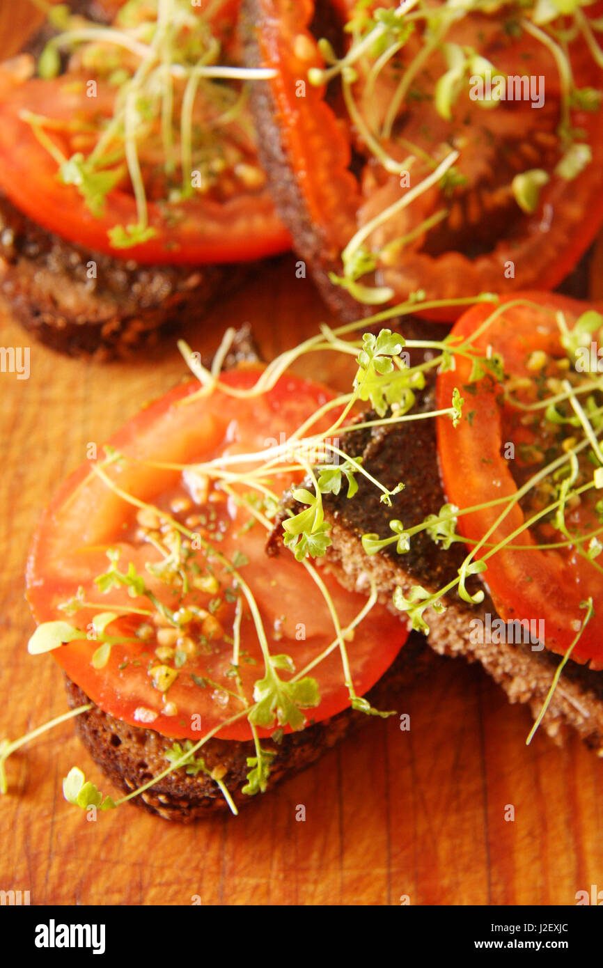 Sandwiches with hemp butter and tomatoes on table Stock Photo