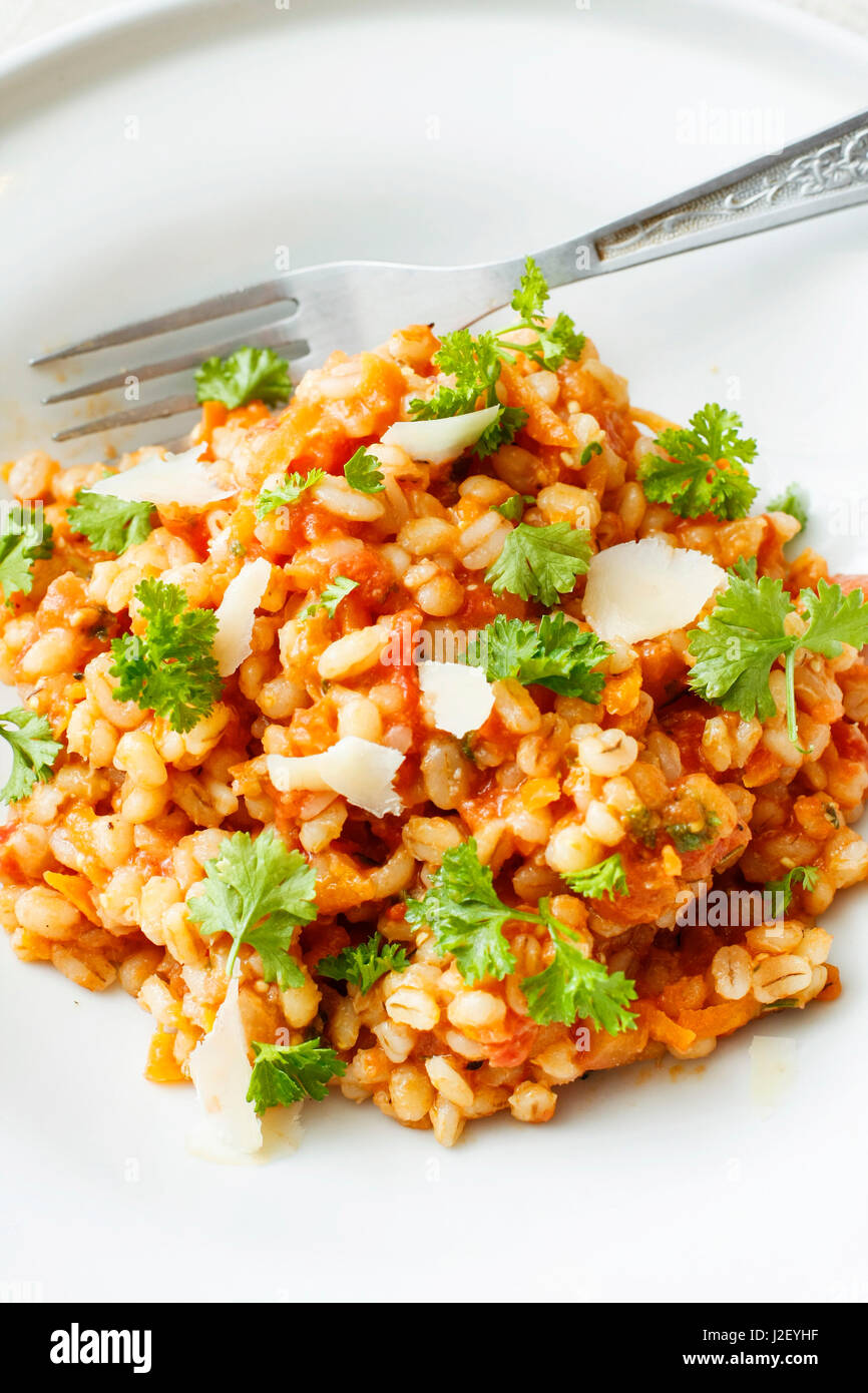 Pearl barley and tomato stew on white platter Stock Photo