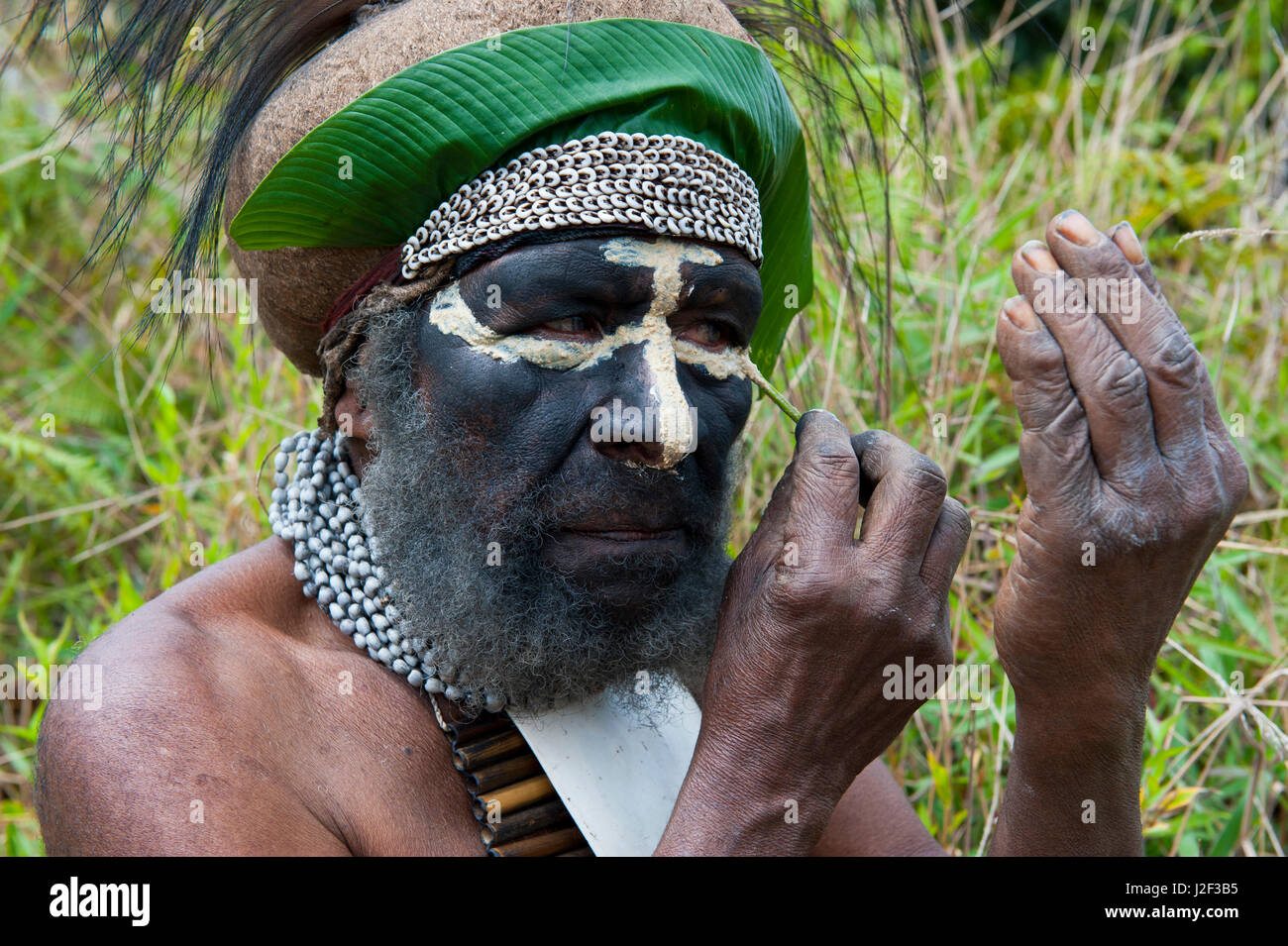 Colorfully dressed local tribal chief painting his face in the Highlands of Papua New Guinea, Melanesia - Stock Image