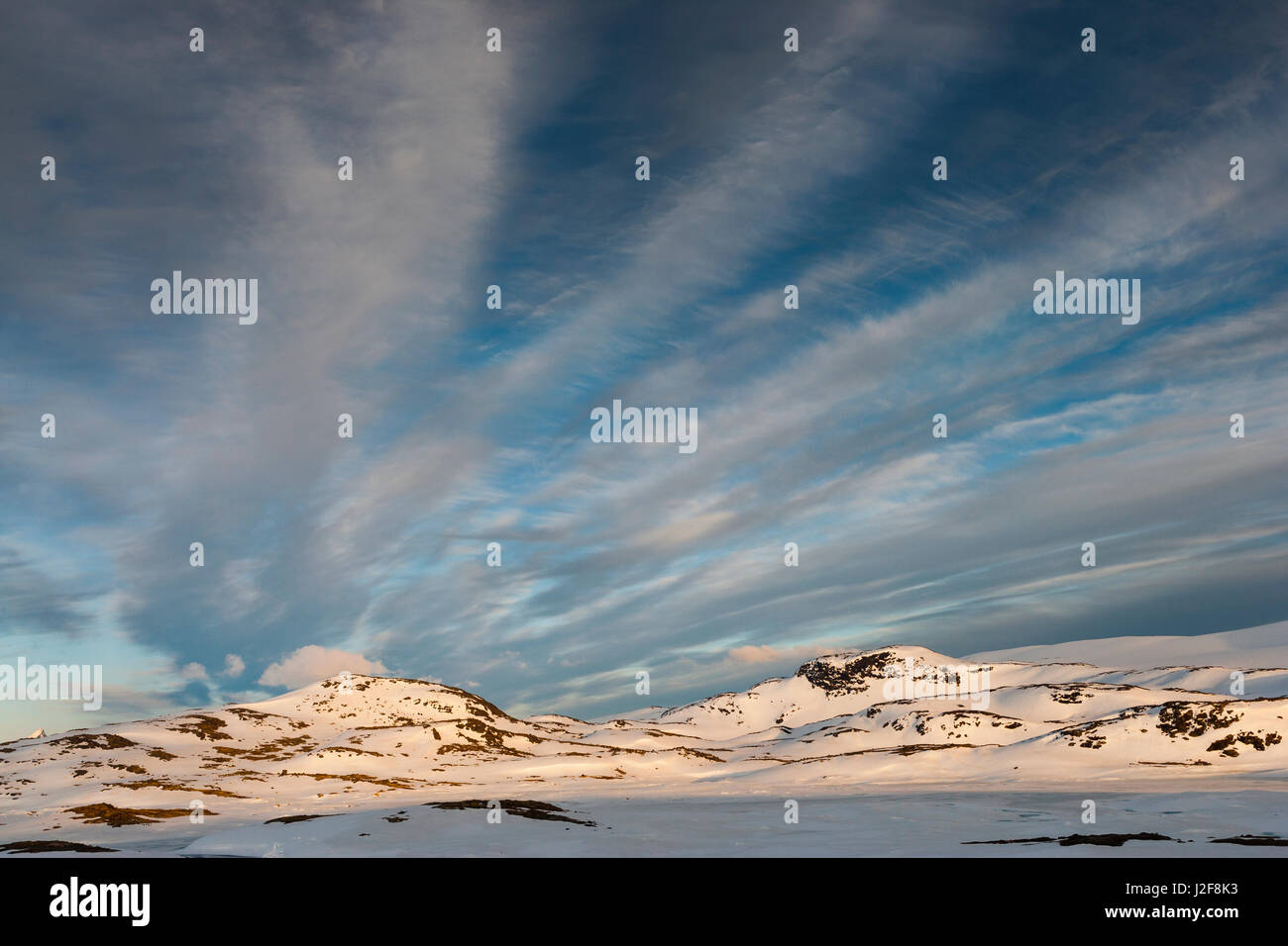 Mountains of Jotunheimen in evening light under a sky with cirrus clouds - Stock Image