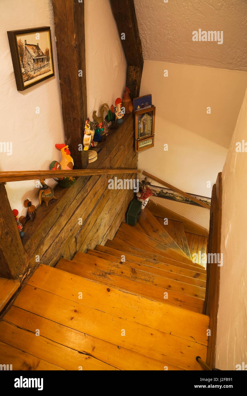 Wooden staircase leading to the ground floor inside a reconstructed (1976) cottage style log home. - Stock Image