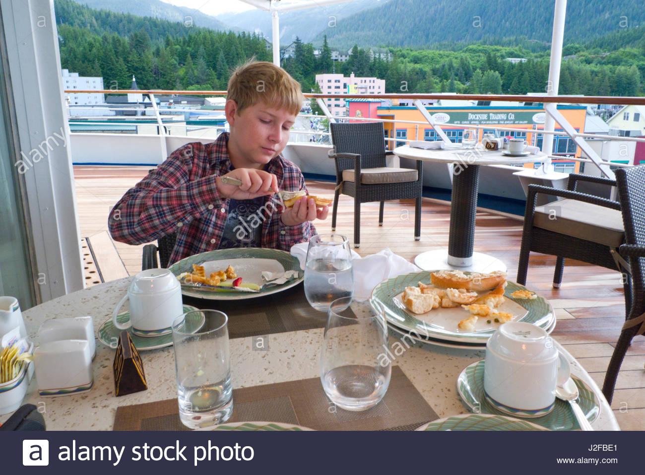 Young teenage Caucasian boy eating breakfast on the Regency Seven Seas Navigator, Ketchikan, Alaska, USA - Stock Image