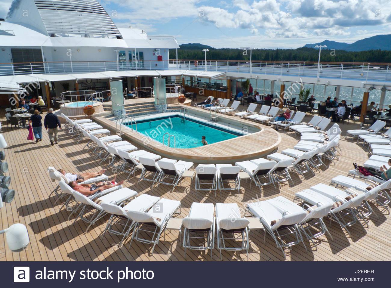Lounge chairs around pool on the Regency Seven Seas Navigator Cruise Ship docked at Ketchikan harbor, Alaska, USA - Stock Image