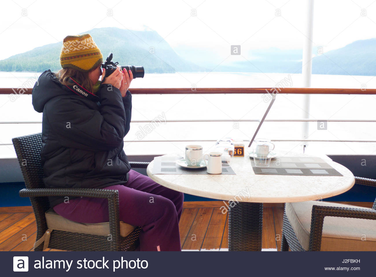 Woman wearing a jacket seated at table taking a photograph with her Digital DSLR camera on the Regency Seven Seas - Stock Image