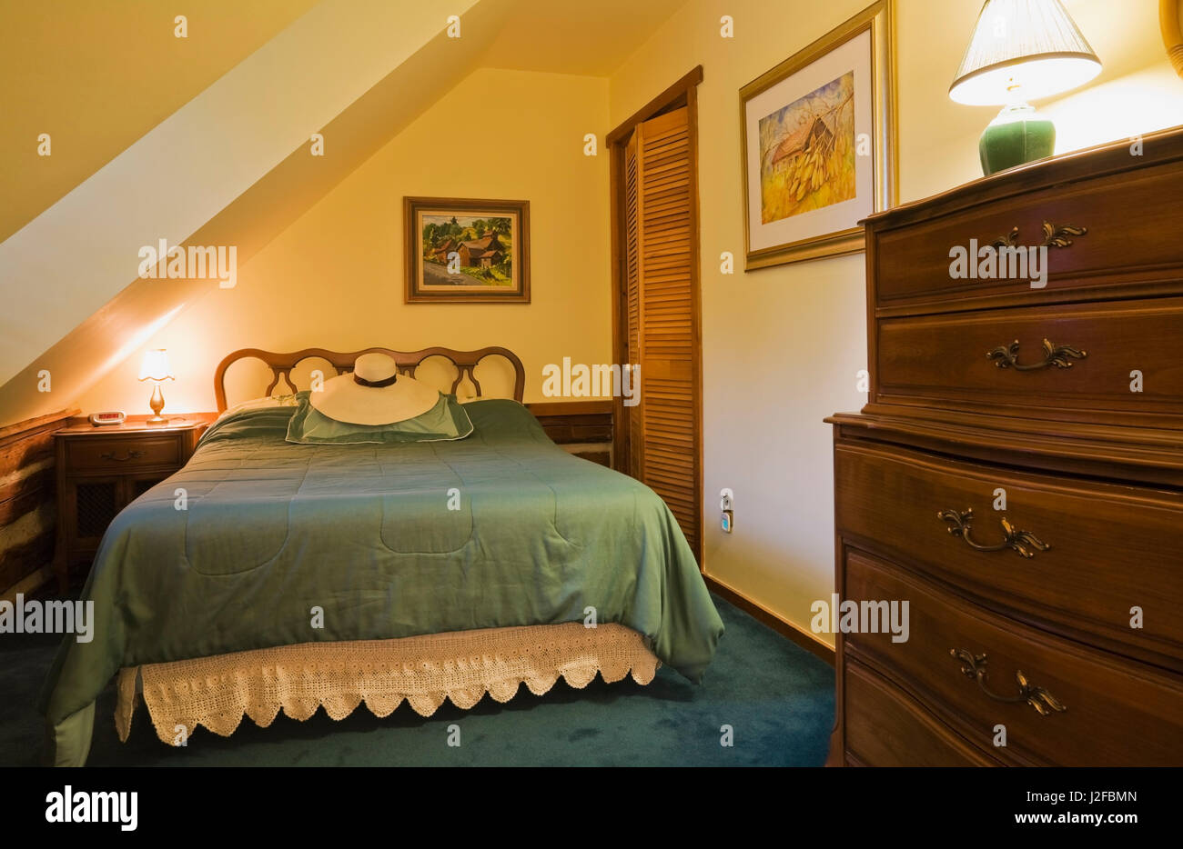 Queen size bed and old wooden dresser in guest bedroom on the upstairs floor inside a 1976 reconstructed cottage style log home Stock Photo