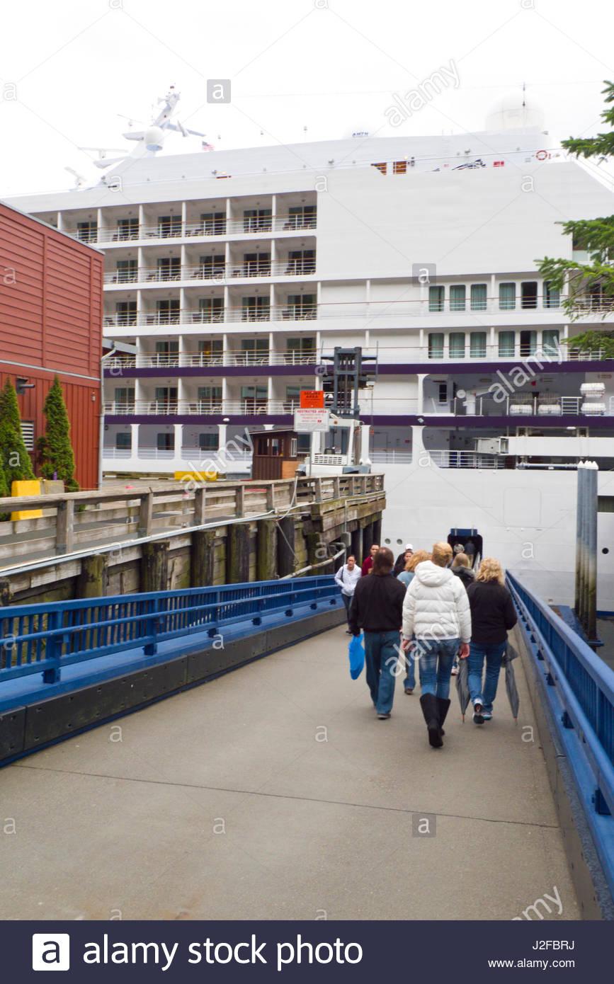 People walking down gangway to the entrance of the Regency Seven Seas Navigator cruise ship, Juneau, Alaska, USA - Stock Image