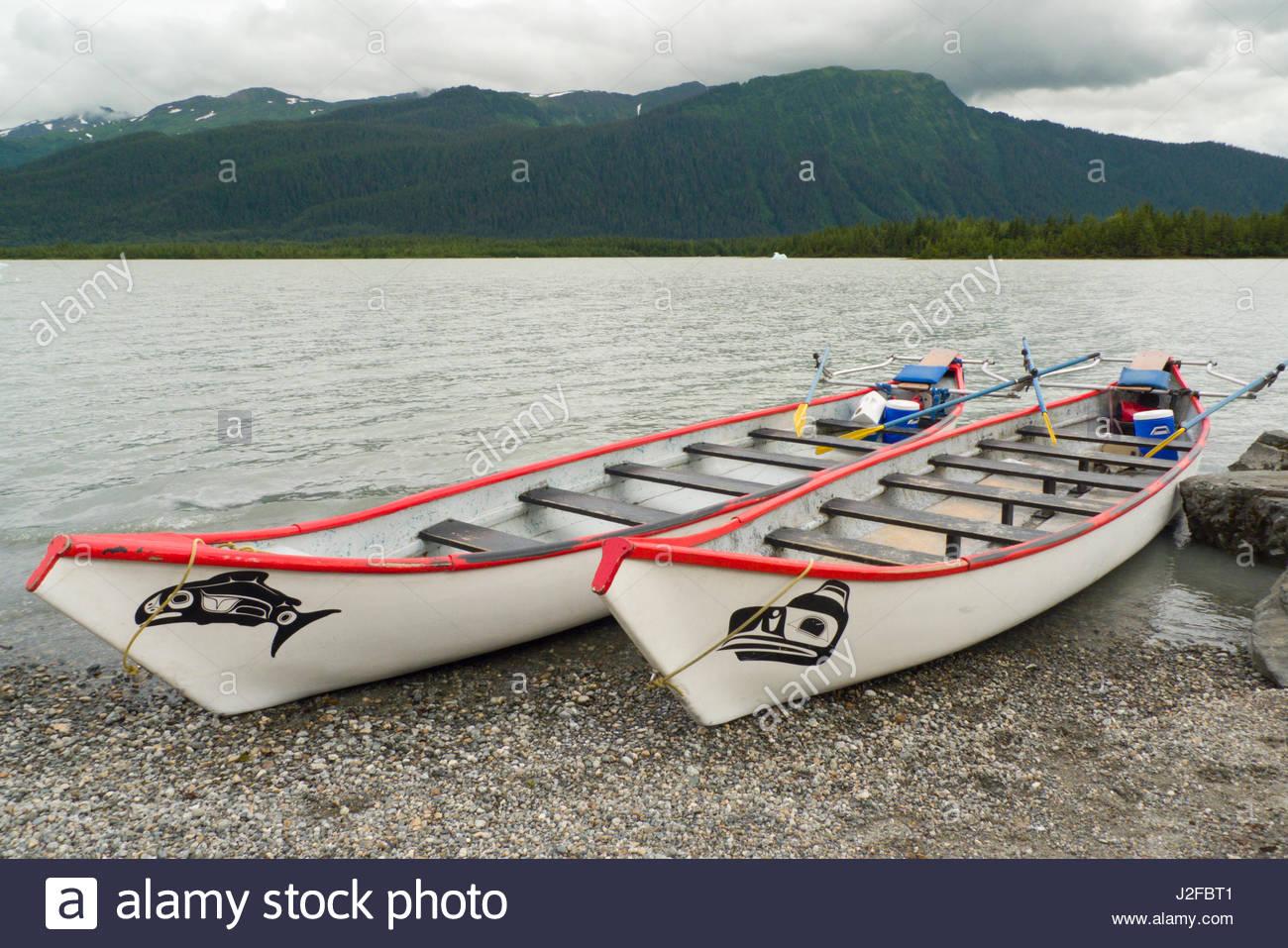 Two large fiberglass canoes on the gravel shoreline of Mendenhall Lake, Tongass National Forest, Juneau Borough, Stock Photo