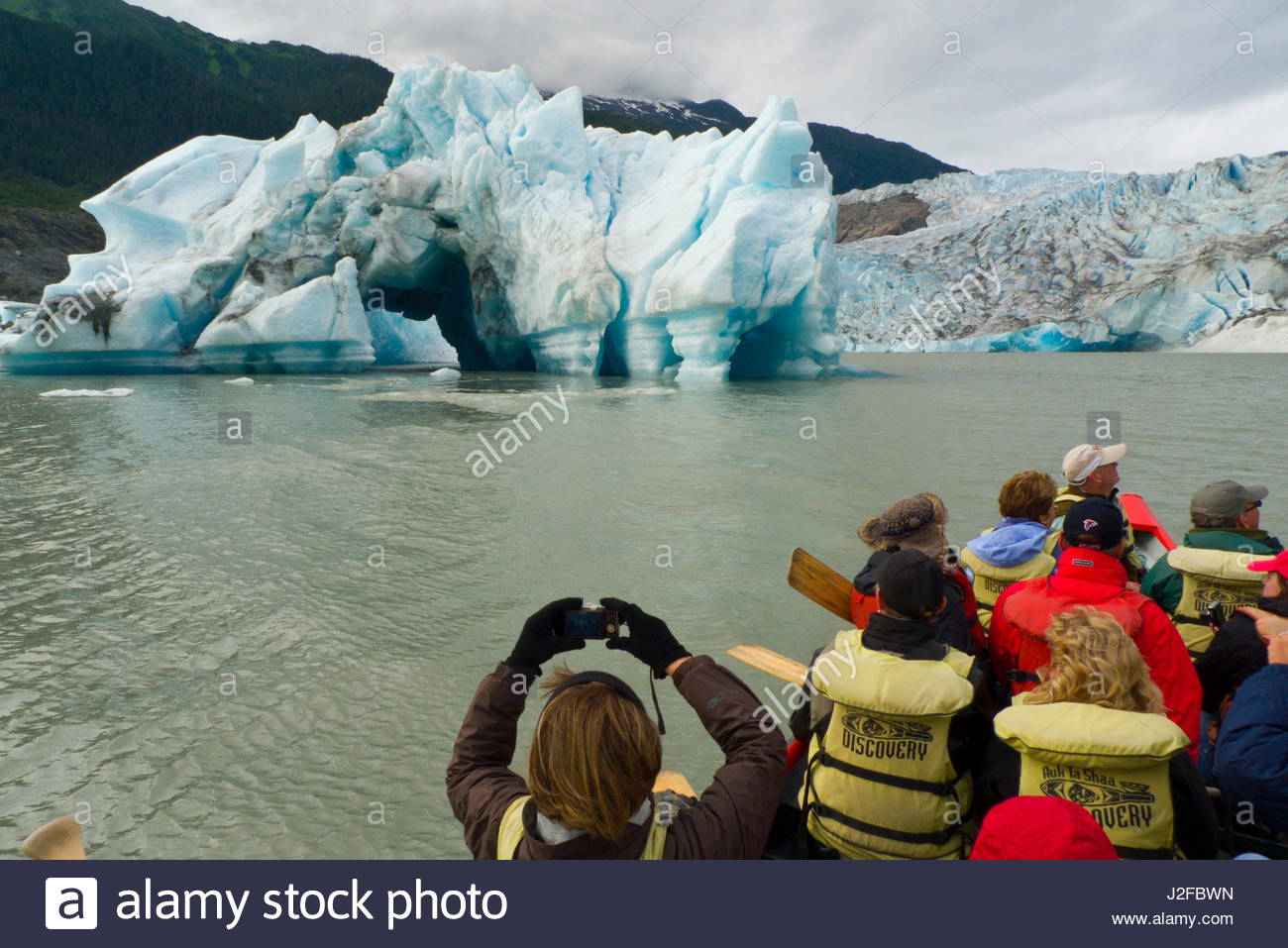 Group of tourist on a large fiberglass canoe on Mendenhall Lake looking at Mendenhall Glacier, Tongass National - Stock Image