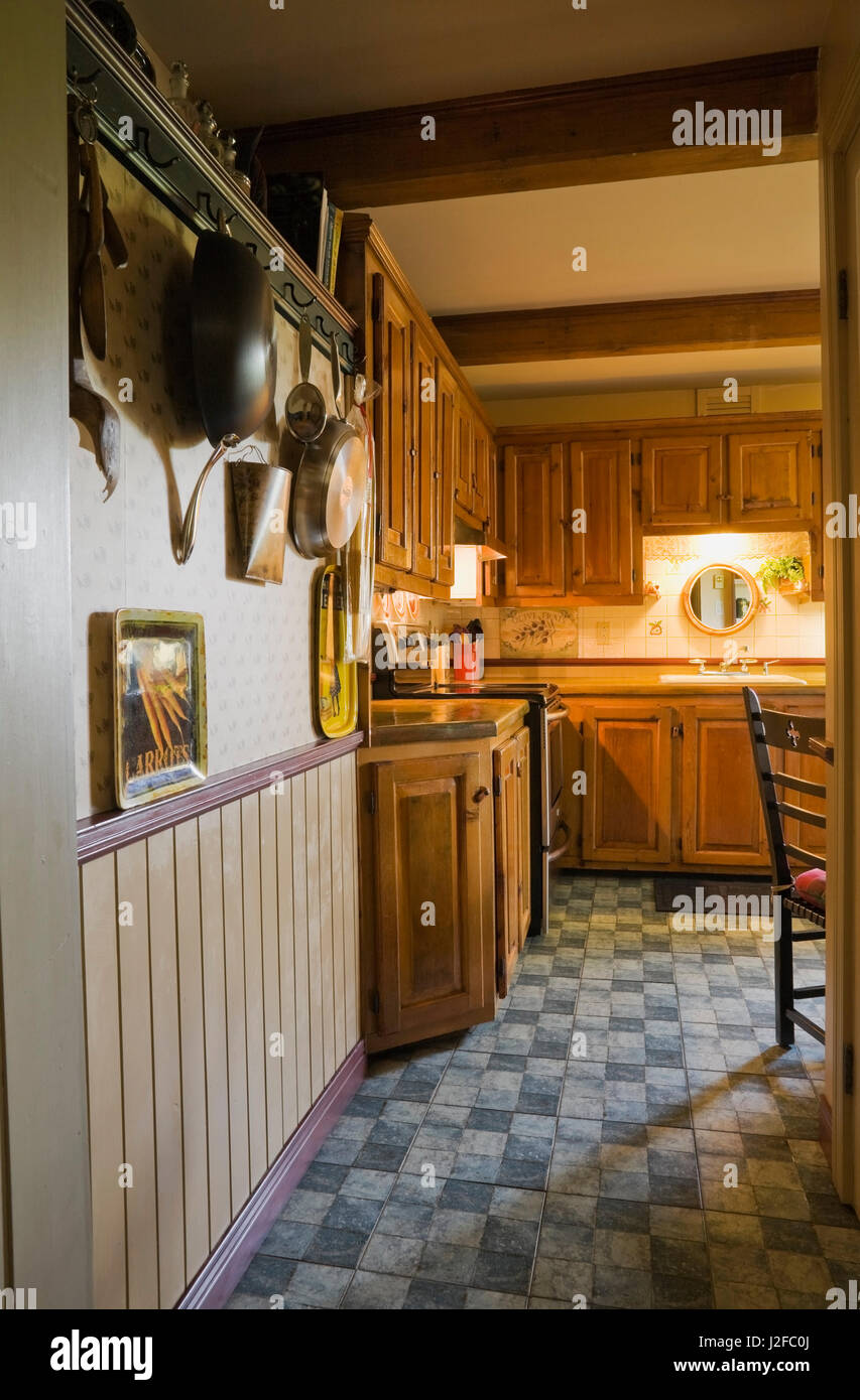 Hallway leading to rustic kitchen with wooden cabinets inside an old reconstructed 1850s cottage style log home Stock Photo