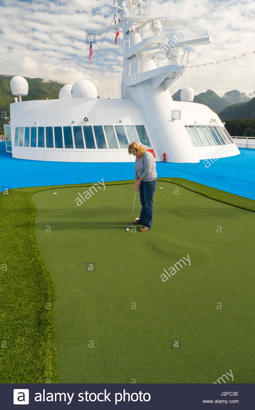 Mature Caucasian woman putting a golf ball on an artificial turf green on the top deck of the Regency Seven Seas - Stock Image