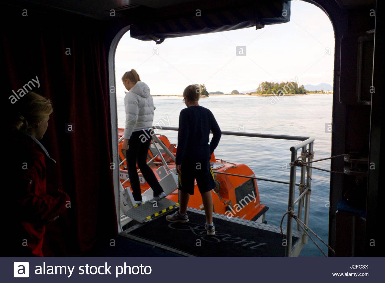 Passengers loading onto orange ship tender that will ferry them to Sitka, Regency Seven Seas Navigator Cruise Ship, - Stock Image