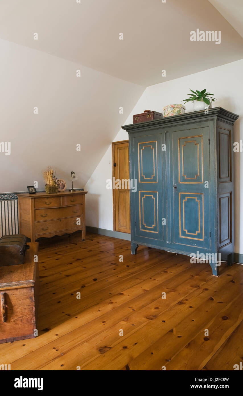 Wooden chest table, dresser and blue painted armoire in guset bedroom on the upstairs floor inside an old reconstructed - Stock Image