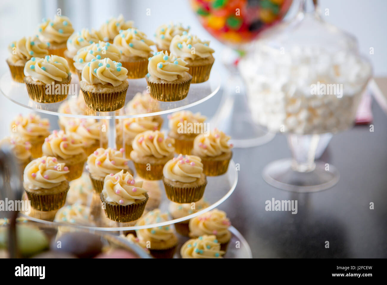 Vanilla bean mini cupcakes decorated with cyan and pink candy beads on clear tiered tray on a dessert table with - Stock Image