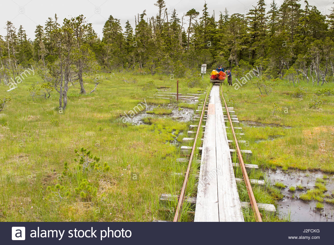 Men pushing tram loaded with plastic kayaks on portage from Oliver Inlet to Seymour Canal, Admiralty Island National - Stock Image
