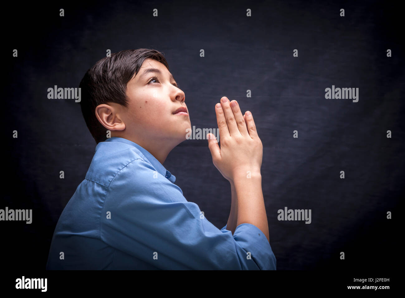 A young boy folds his hands and raises his head in prayer to God. - Stock Image