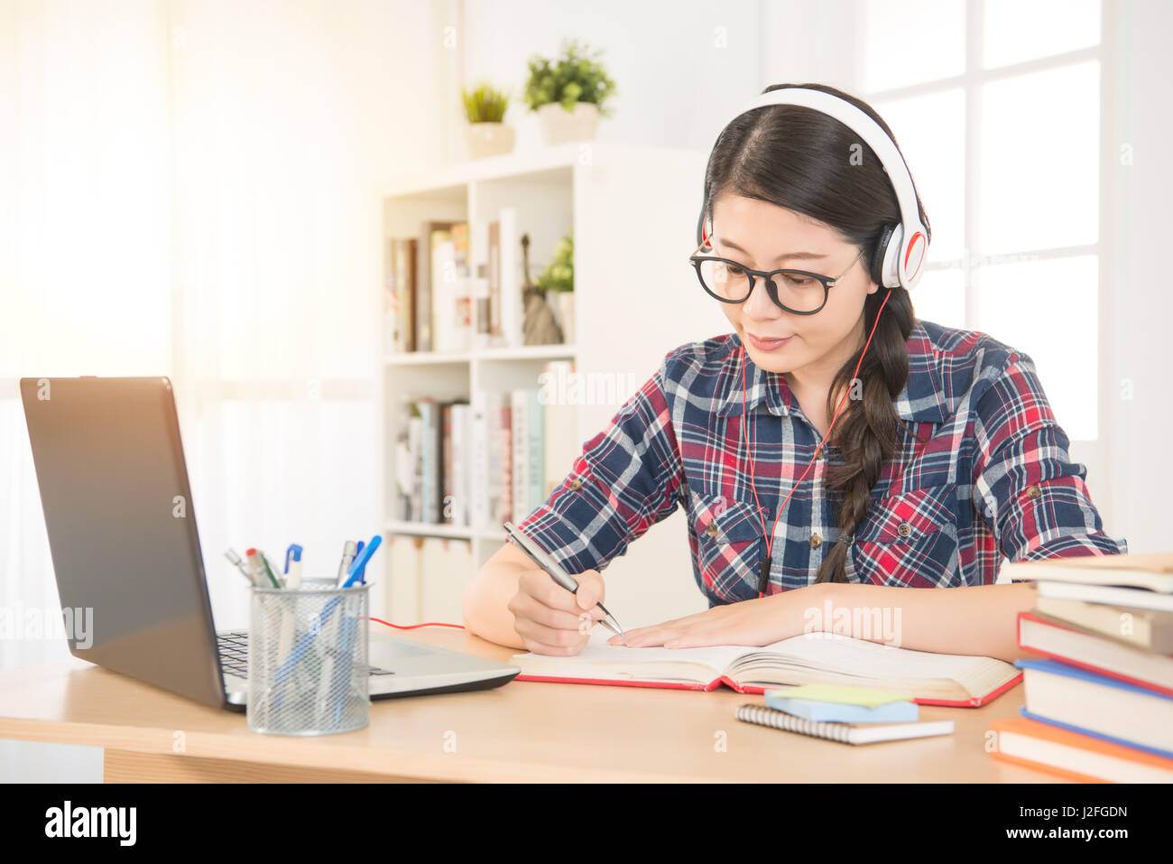 Portrait of a student learning on line with headphones and laptop taking notes in a notebook sitting at her desk - Stock Image
