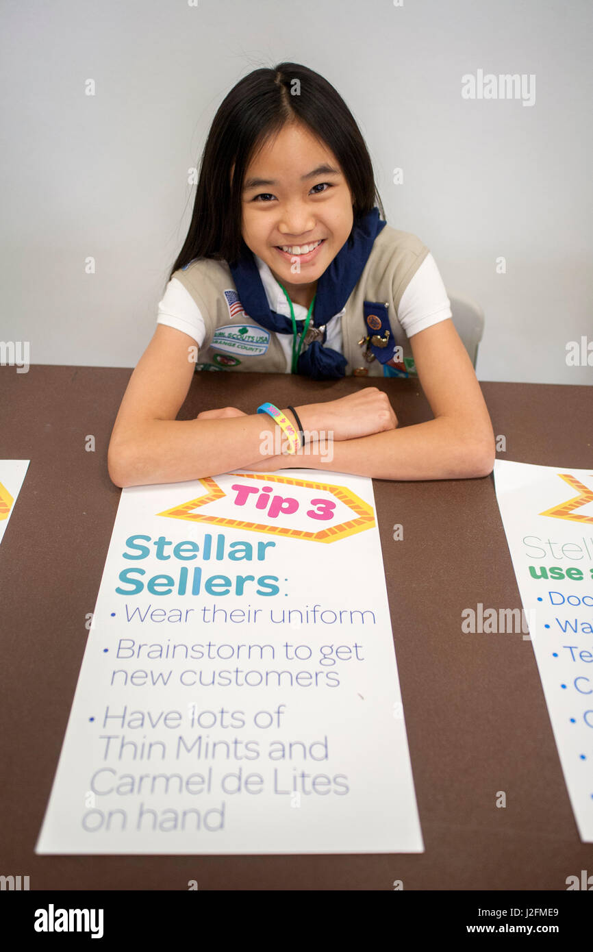 An Asian American champion Girl Scout cookie seller offers a list of selling tips to other scouts at a selling workshop - Stock Image