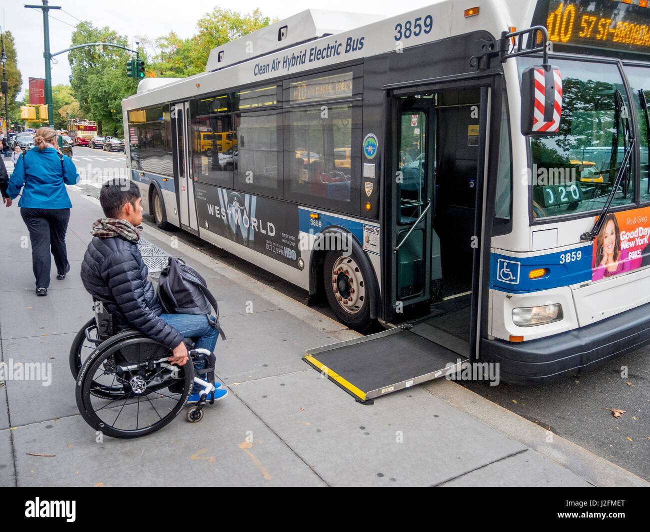 a city bus extends a handicapped ramp for a wheelchair user at a bus