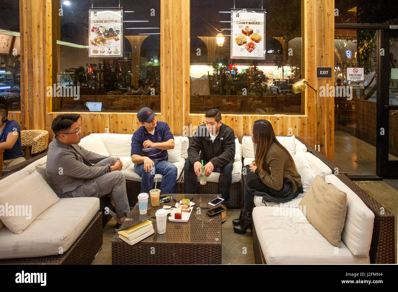 Four Asian American young adults relax on couches as they enjoy coffee and pastries at an European style cafe in - Stock Image