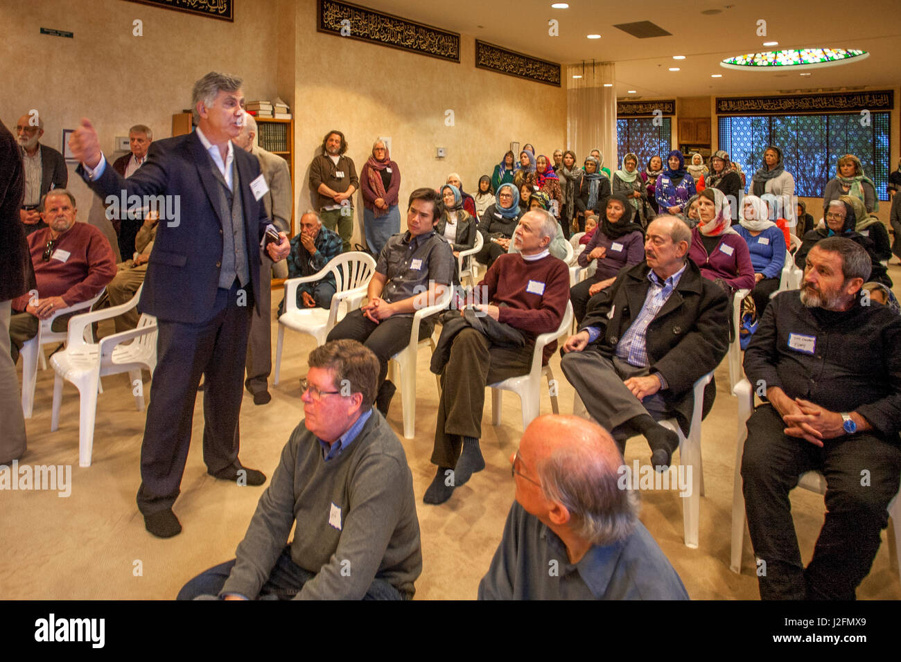 A guide lectures on Islam to non-Muslim local community visitors to a mosque on visitors day in Mission Viejo, CA. - Stock Image
