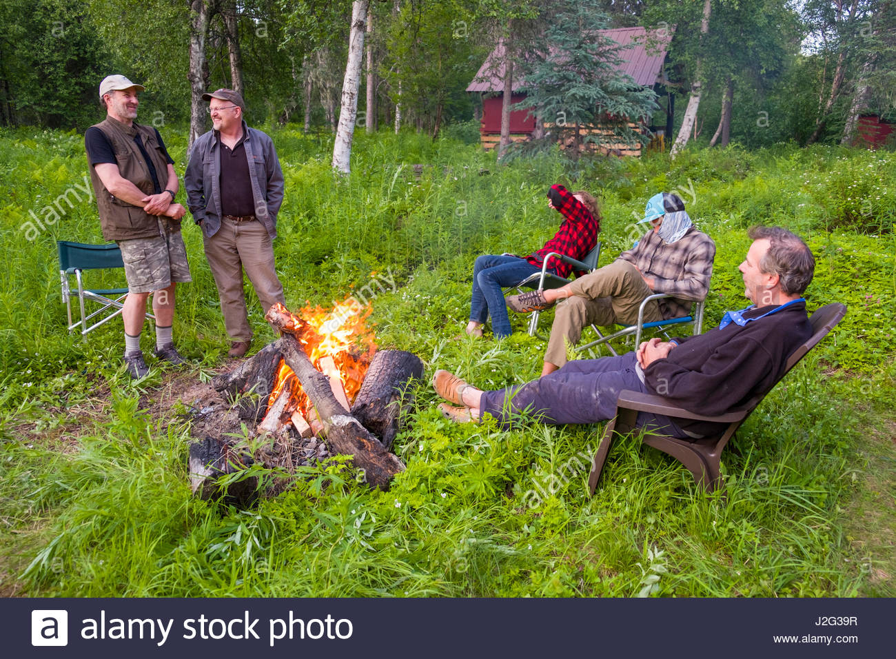 Men standing and sitting around campfire at remote off ...