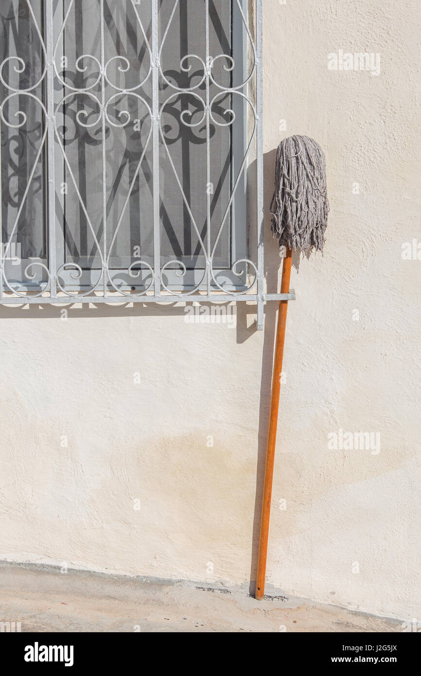 A mop stood outside a window of a house. Minimalist composition. - Stock Image