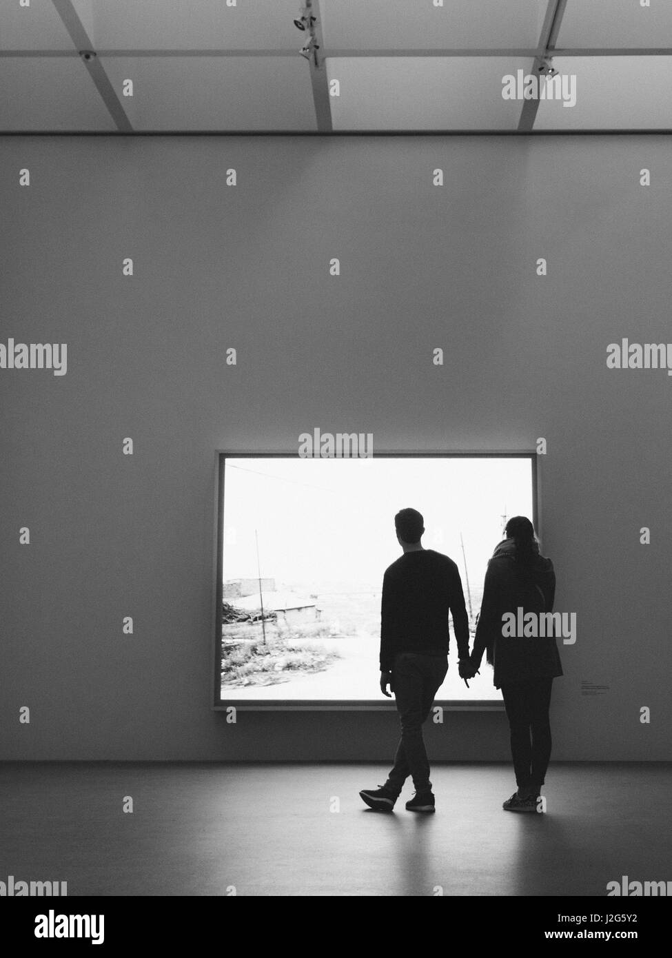 A silhouette of a male and female couple looking at an exhibit in an art museum - Stock Image