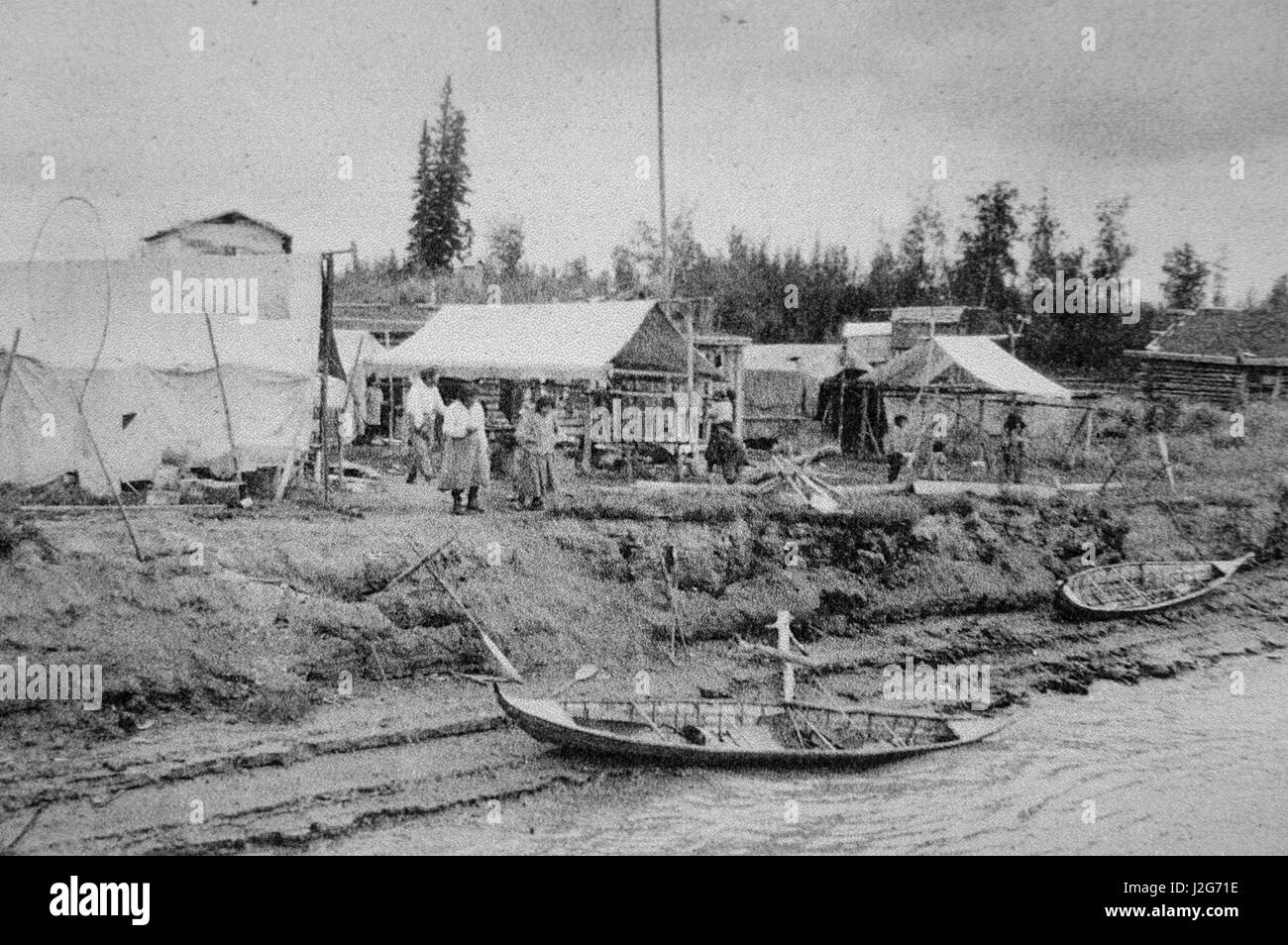 Historic black and white photograph of Athabaskan fishing village with birchbark canoes on river banks. Alaska - Stock Image