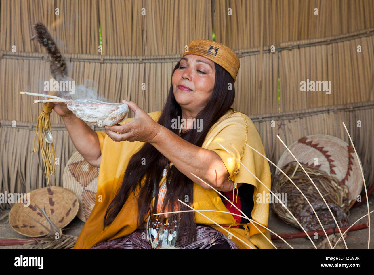 Native woman of the Acjachemen Nation (San Juan Capistrano Mission Indians) burns dried sage in an abalone shell and uses a feather to distribute the smoke which is used as a cleansing medicine inside of a traditional Tule reed shelter. (MR)