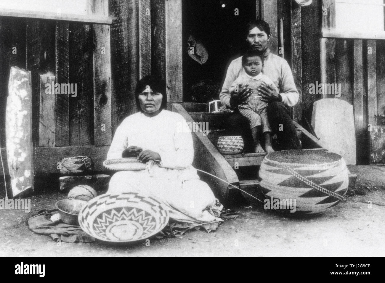 Historic 1892 black and white photograph of a Pomo basket maker sitting outside with her family, California - Stock Image