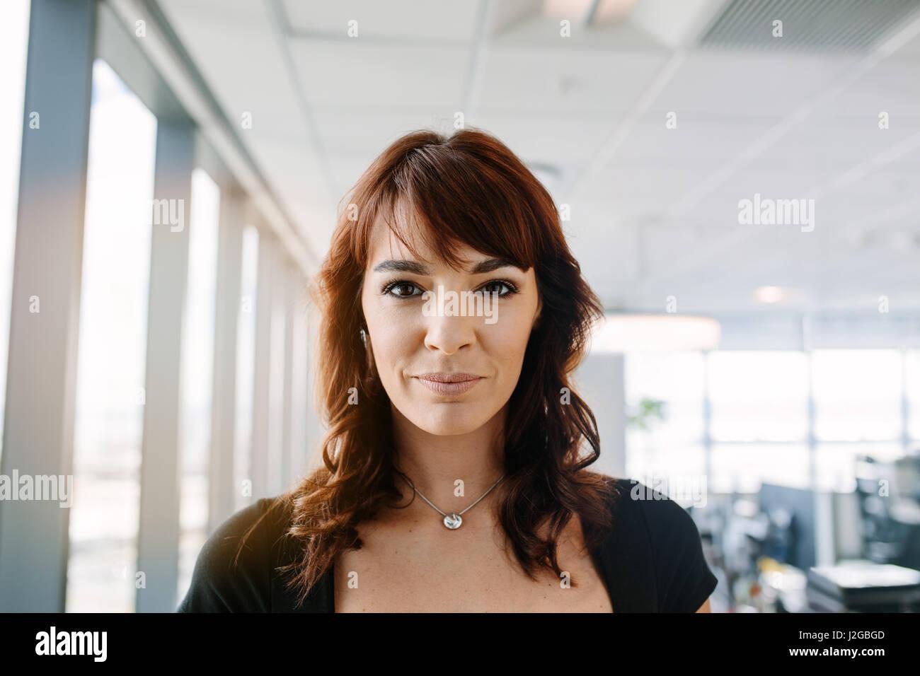 Close up portrait of beautiful mature businesswoman standing in office. Caucasian female corporate professional - Stock Image