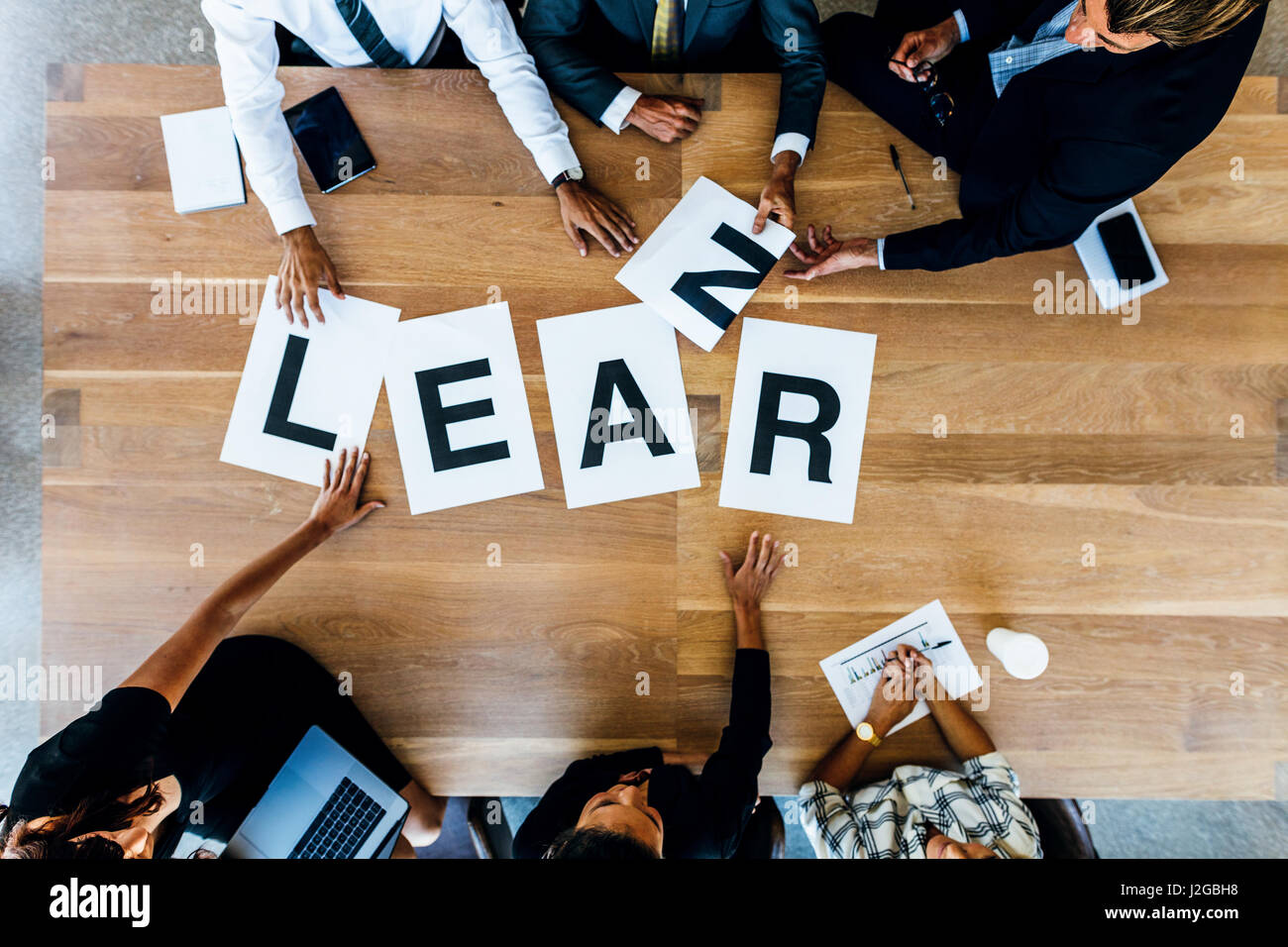 Group of people placing signs with alphabets forming the word learn on table. Business people discussing over learning - Stock Image