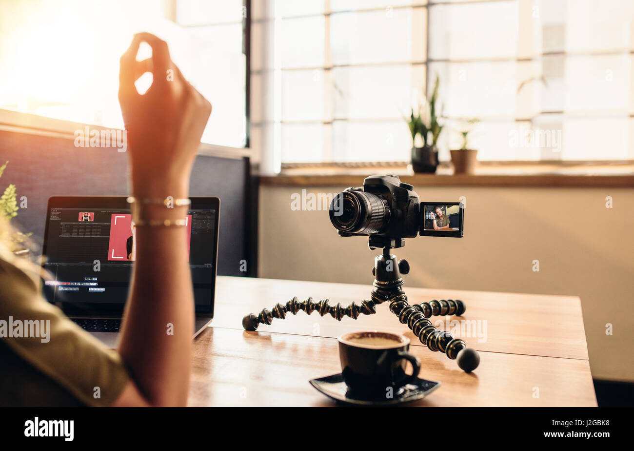 Female vlogger looking at camera while editing video on her laptop. Young woman working on computer with coffee - Stock Image