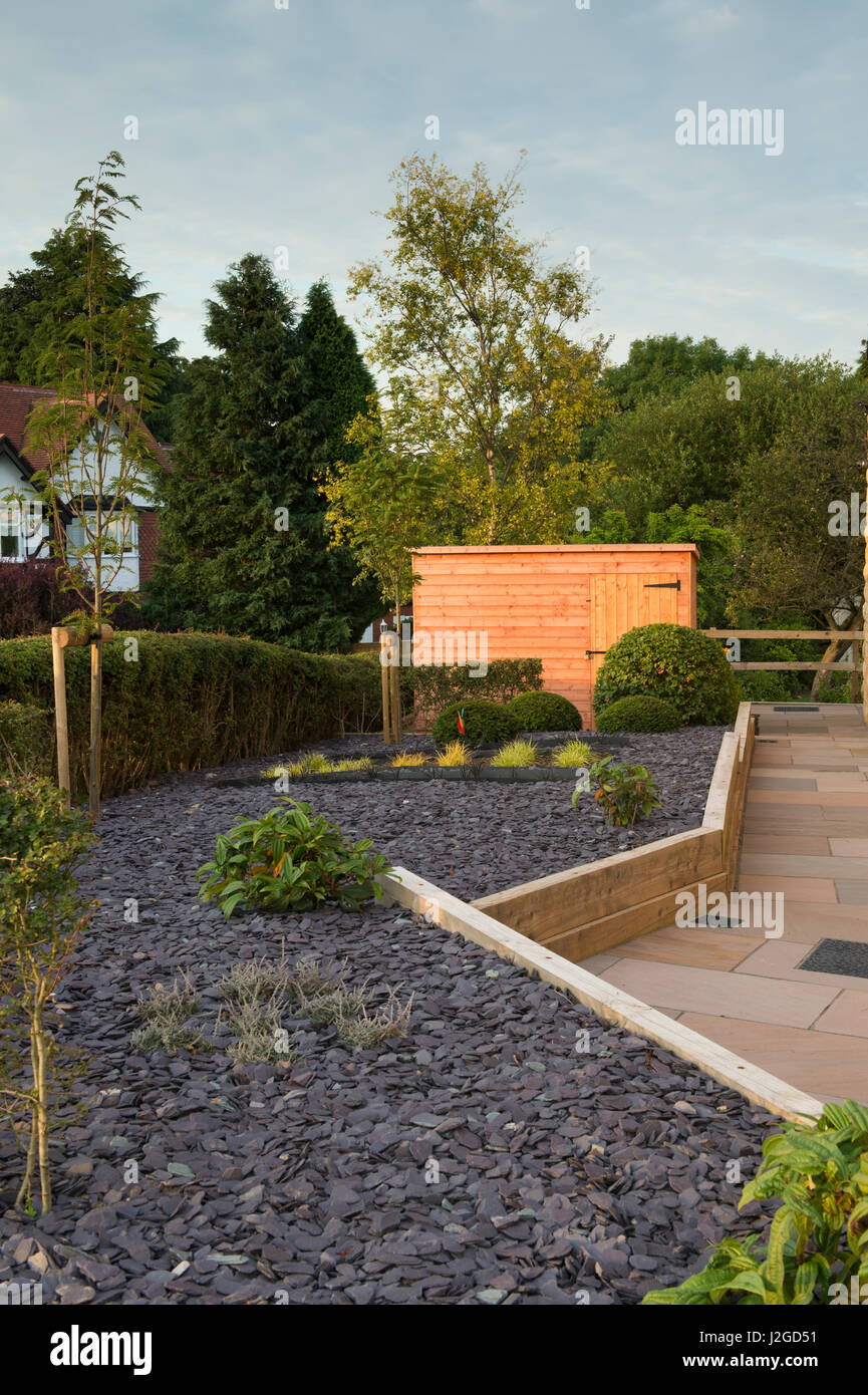 Beautiful, private garden, Yorkshire, England, UK - stylish, contemporary design, hard landscaping (paving) shed Stock Photo