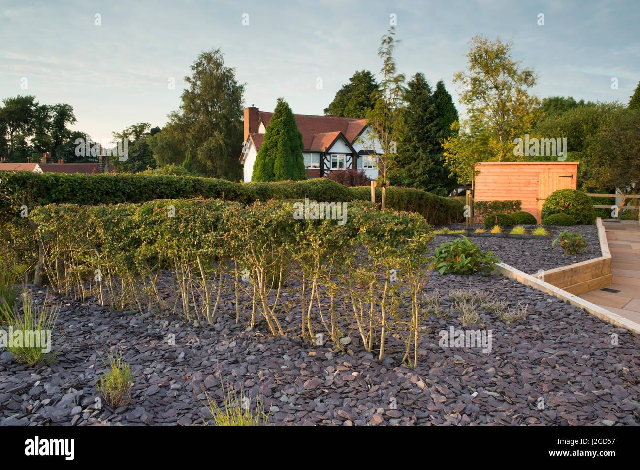 Beautiful, private garden, Yorkshire, England, UK - stylish, contemporary design, hard landscaping (paving) shed - Stock Image