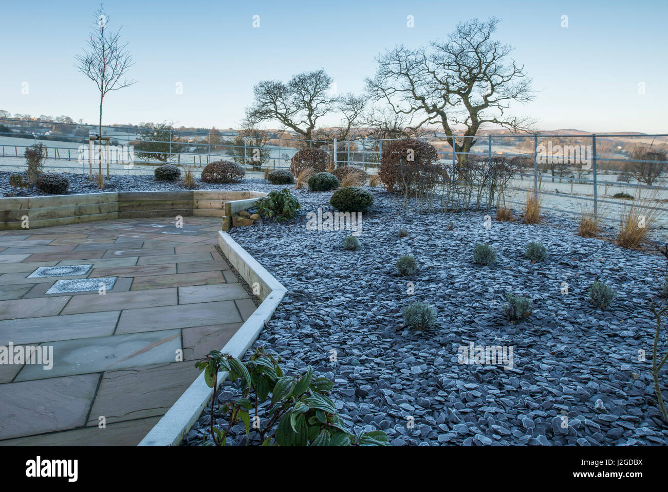 Winter frosty view of private garden, with stylish, contemporary design,  hard landscaping and new planting on raised - Stock Image