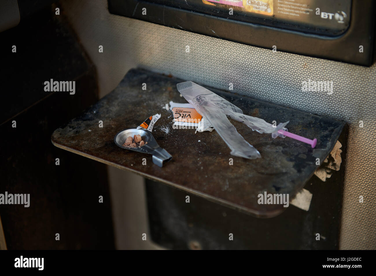 Debris left by a drug user in a phone box in Cardiff - Stock Image