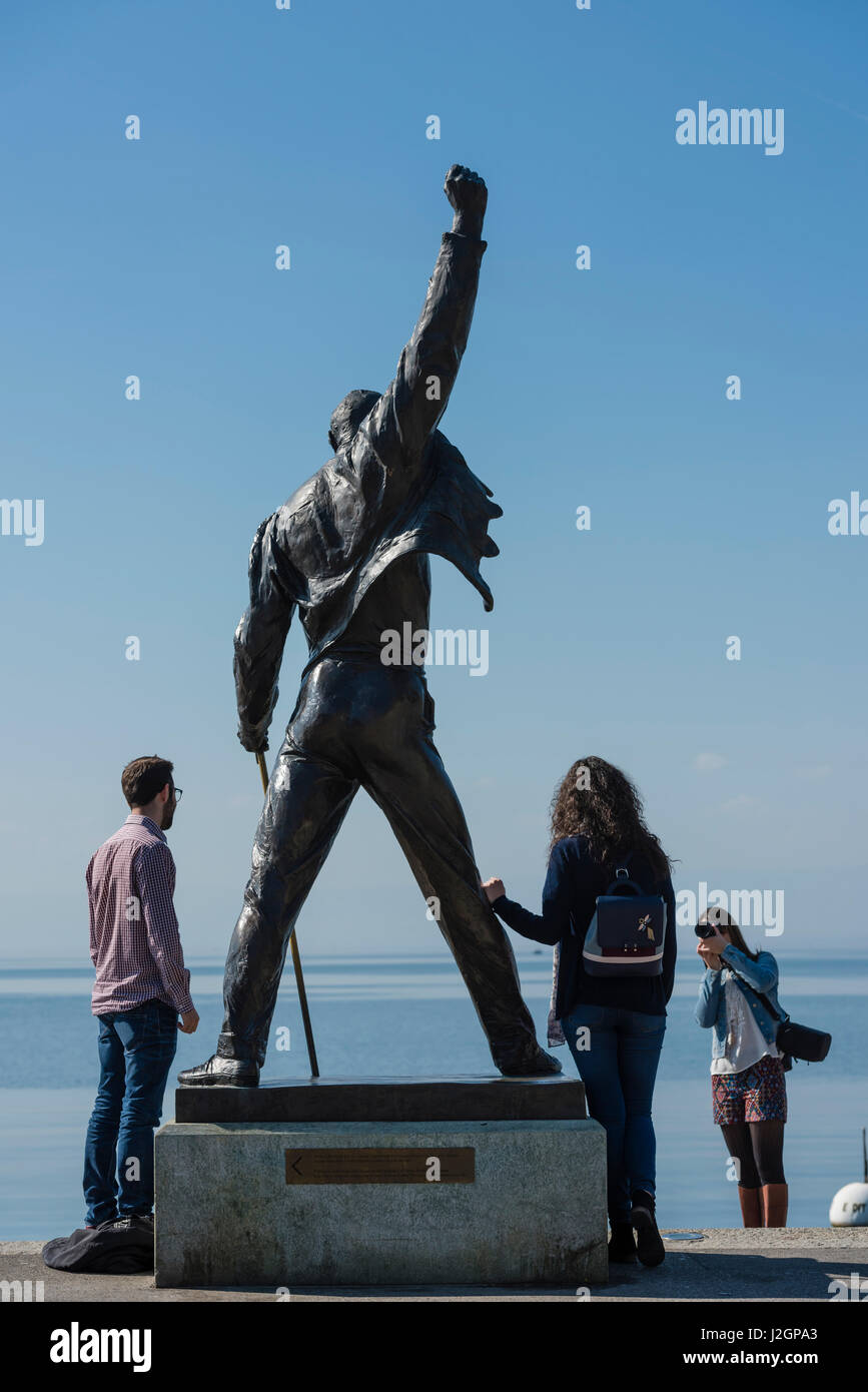 Tourists are posing for a photo with the statue of Freddie Mercury, late singer of the UK rock band Queen, at the Stock Photo