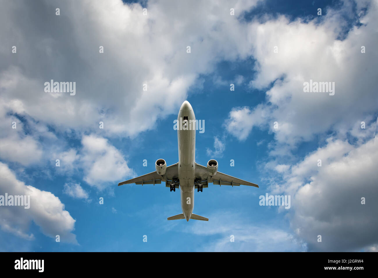 big jet plane on blue cloudy sky background - Stock Image