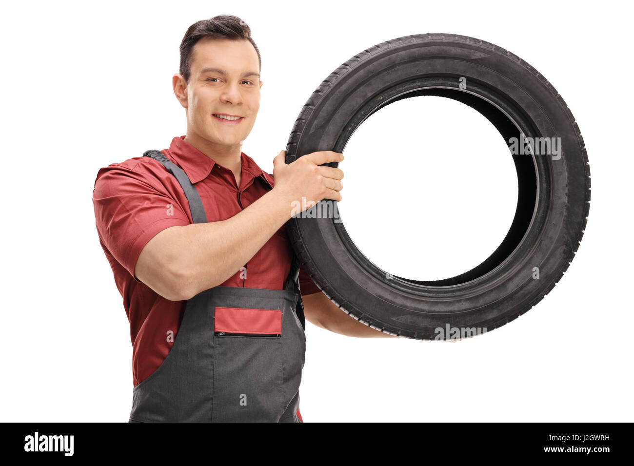 Young mechanic with a tire looking at the camera and smiling isolated on white background - Stock Image